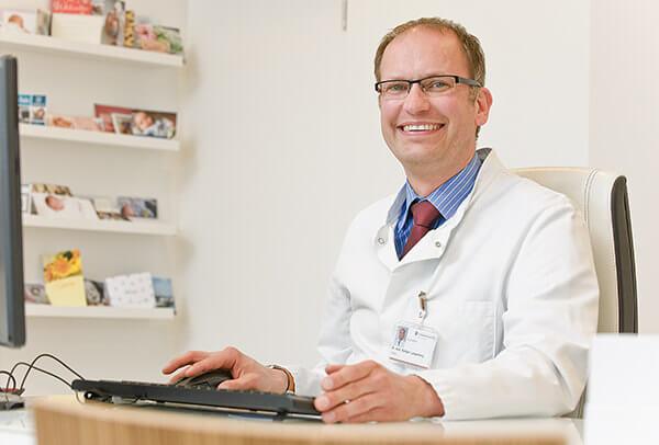 Herrn Dr. med. Rüdiger Langenberg, Chefarzt der Frauenklinik in seinem Büro vor einem Computer sitzend