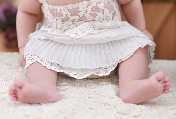 Baby am sitzen. Man kann die Beinchen sehen