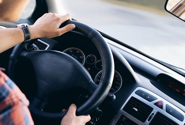 Männerhand an einem Autolenkrad
