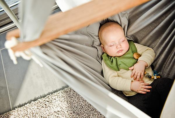 Ein Baby schläft sehr ruhig in der grauen NONOMO Federwiege