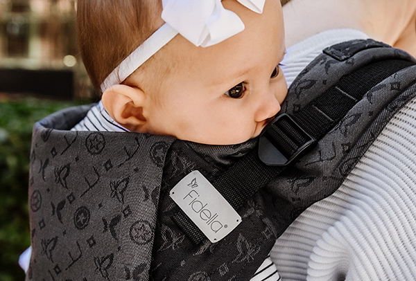 Baby with white hairband is carried in a black baby carrier by Fidella.