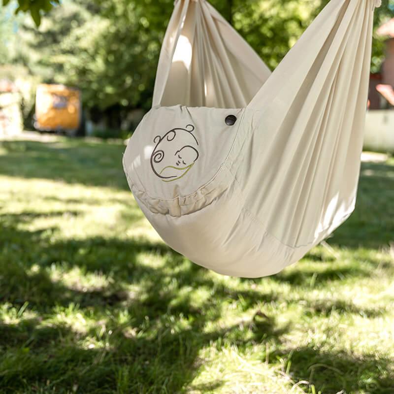 Swinging hammock hangs outside on a tree