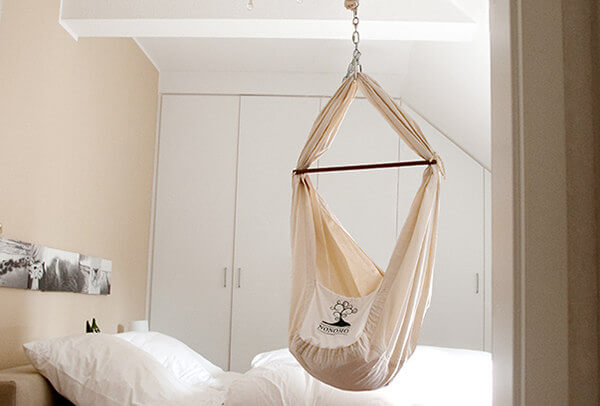 The old variant of a feather cradle hanging in a bedroom